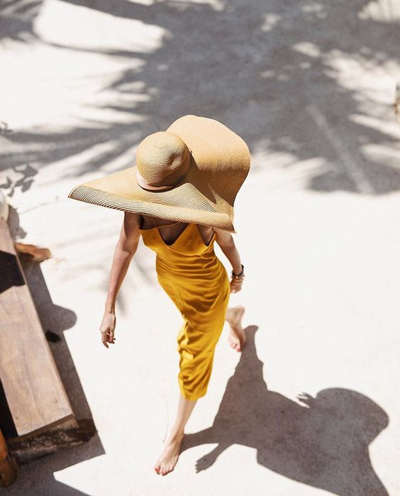 a refined vacation look with a bright yellow midi dress with a catchy neckline and an oversized hat