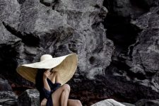 11 a black long coverup over a swimsuit paired with an oversized hat will create a wow effect