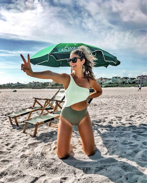 a bold one piece one shoulder cutout swimsuit with a white top and a green bottom