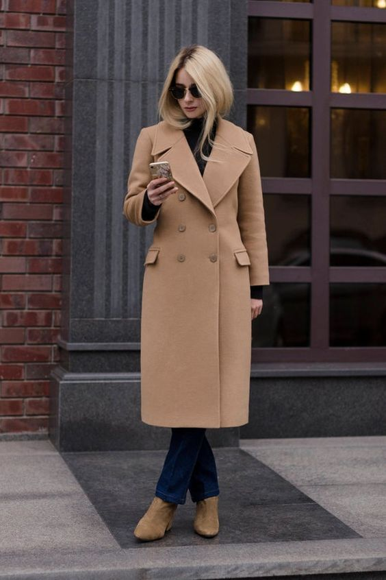 a simple fall look with a black turtleneck, navy jeans, tan booties, a camel coat is stylish