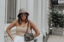 12 a summer look with a nude spaghetti strap top, white pants, a black bag and a snake print bucket hat