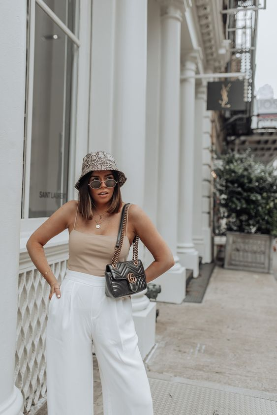 a summer look with a nude spaghetti strap top, white pants, a black bag and a snake print bucket hat