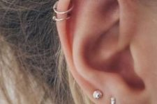 13 elegant ear accessorizing with minimalist gold studs and gold hoop earrings in the double helix piercing