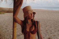 14 a red bikini with ties, layered necklaces, a straw bucket hat and a woven bag
