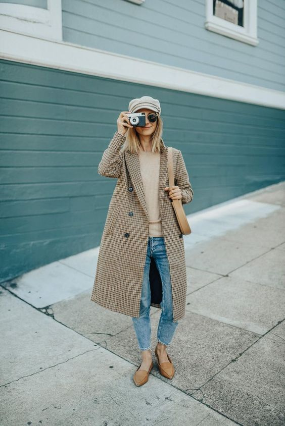 a relaxed fall outfit with a tan top, blue jeans, tan mules, a plaid double breasted coat and a neutral cap
