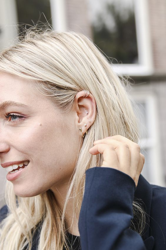 upper helix piercings with delicate silver hopp earrings look chic and cool