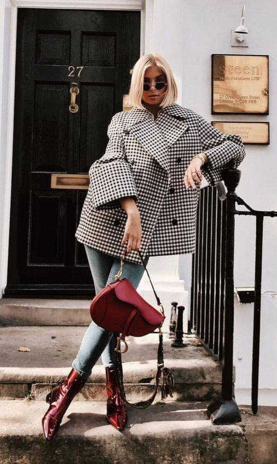 a plaid double breasted coat, blue jeans, red lacquer booties and a red saddle bag