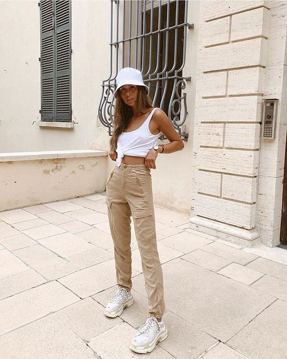 a summer outfit with a white tied up tank top, tan cargo pants, white trainers and a white bucket hat