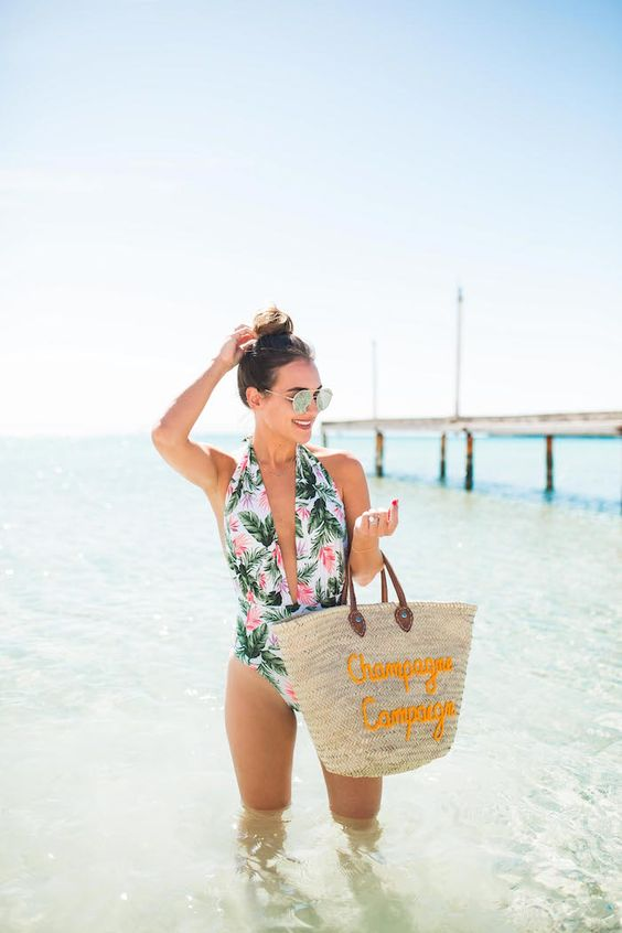 a bright tropical print one piece swimsuit with a plunging neckline is a bold and trendy idea