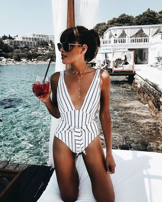 a chic striped one piece black and white swimsuit with a plunging neckline, ties and a boho necklace
