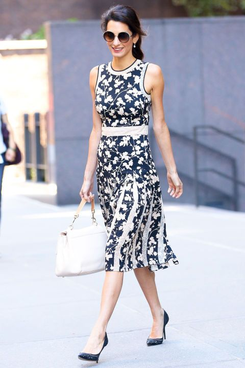 Amal Clooney wearing a romantic monochromatic sleeveless floral midi dress and rocking a white top handle bag
