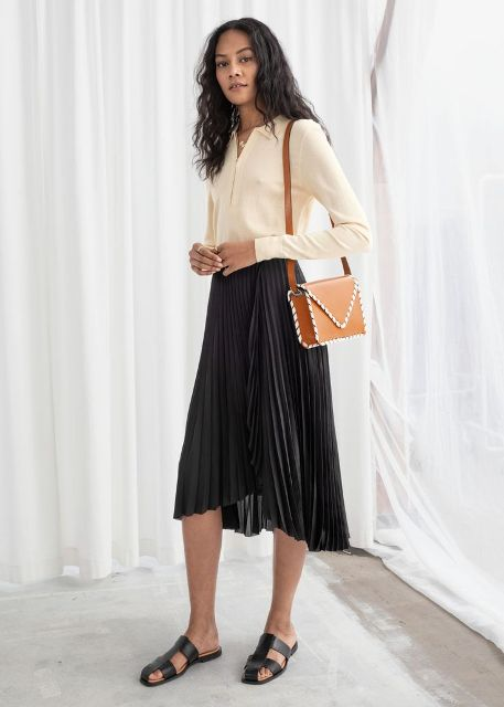 With beige blouse, brown bag and black flat sandals
