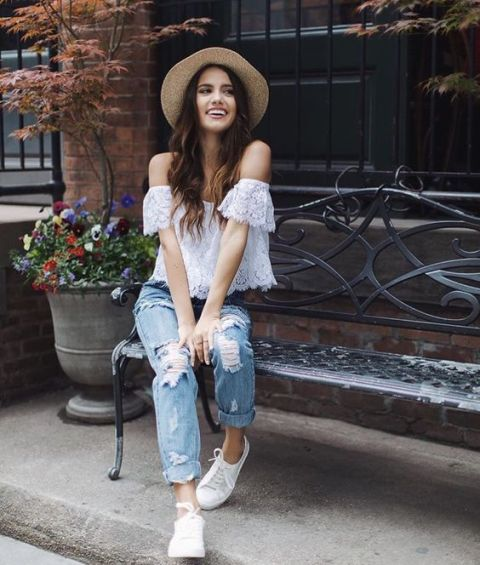 With beige hat, distressed jeans and white shoes