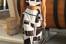 With black and white one shoulder crop top, black bag and black sandals