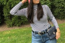 With black and white striped shirt, jeans, black belt and chain strap bag