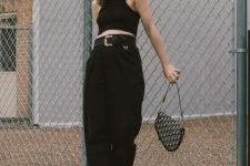 With black crop top, loose trousers, printed bag and lace up boots