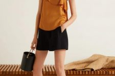 With black shorts, black bag and flat sandals