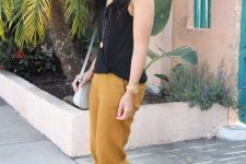 With black sleeveless top, gray bag and yellow cropped pants