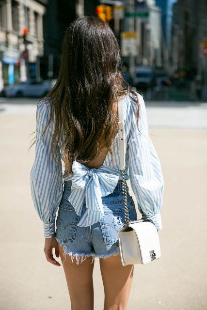 With denim distressed shorts and white chain strap bag