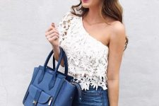 With distressed jeans and navy blue leather bag