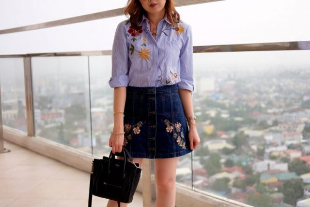 With embroidered shirt and black bag