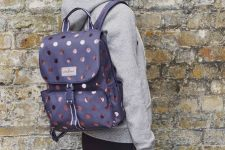 With gray hoodie, sporty pants and polka dot clutch