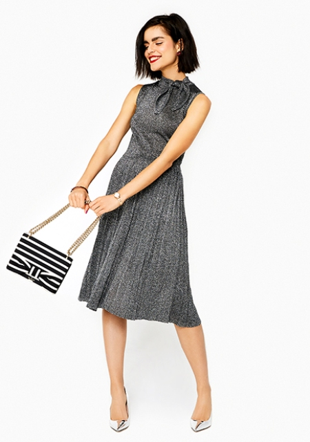 With gray pleated dress and silver pumps