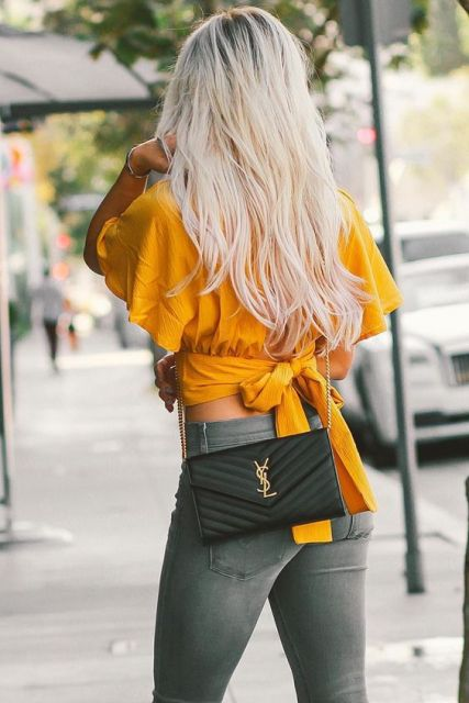 With gray skinny jeans and black chain strap bag