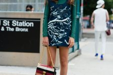 With green shirt, printed mini dress and silver sandals
