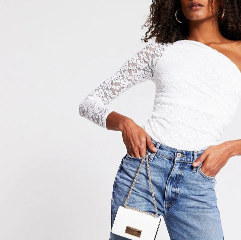 With high-waisted jeans and white chain strap bag