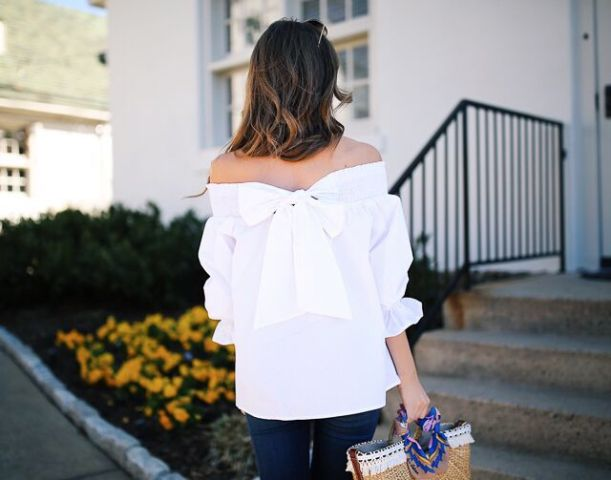 With navy blue jeans and straw tote bag