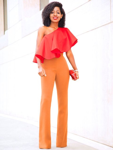 With orange high waisted trousers and red mini clutch