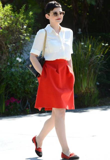 With red knee-length skirt, chain strap bag and red and black shoes
