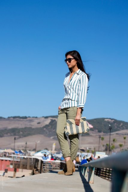 With striped shirt, olive green pants and ankle boots