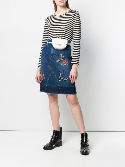 With striped shirt, white waist bag and black ankle boots