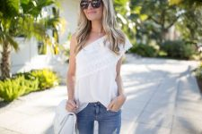 With white chain strap bag and distressed jeans