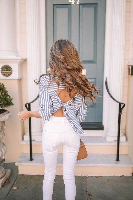 With white high-waisted pants and brown bag