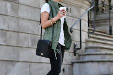With white t-shirt, green vest, black pants and black bag