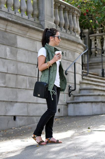 With white t shirt, green vest, black pants and black bag