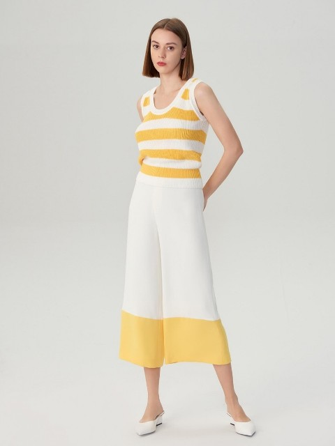 With yellow and white sleeveless top and white low heeled mules