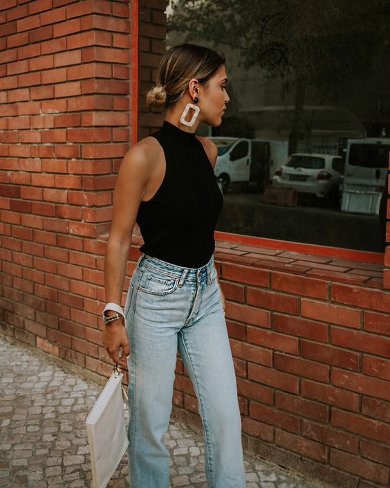 a black halter top, blue high waisted jeans, a large white clutch and statement earrings