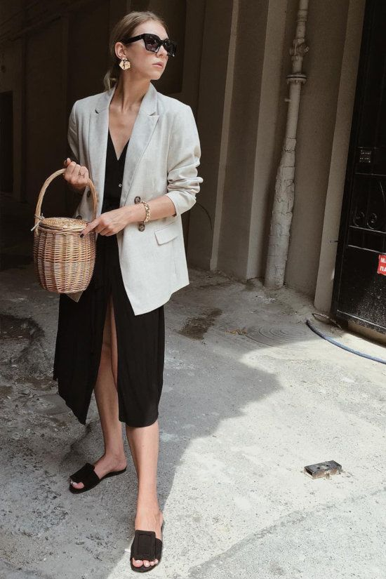 a black midi dress on buttons, a creamy oversized blazer, black slippers and a basket bag