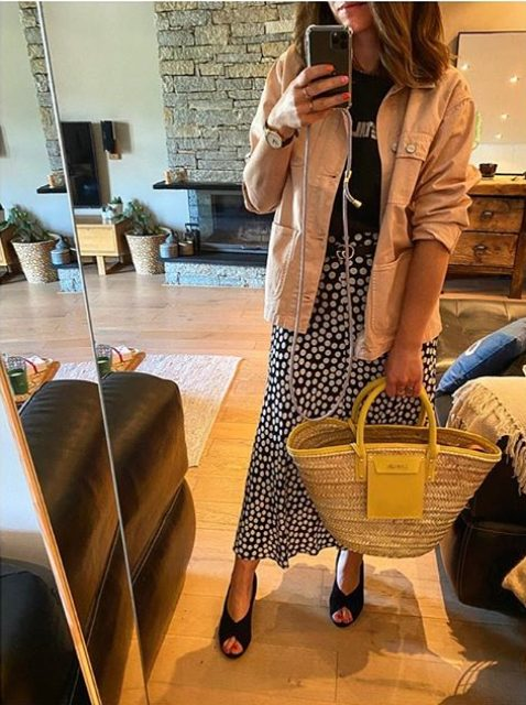 a black printed tee, a polka dot midi skirt, black heels, a tan denim jacket and a hot yellow raffia bag