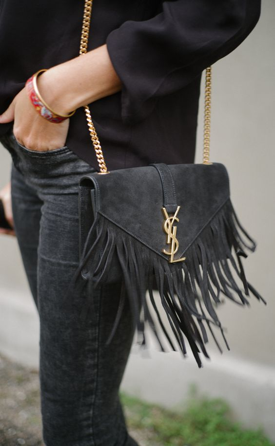 a black suede crossbody bag with long fringe is a nice accessory to carry this fall