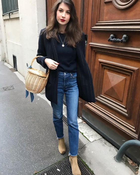 a black top, a black thin stripe blazer, blue jeans, tan Chelsea boots and a basket bag