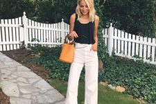 a black top, white raw hem jeans, brown perforated mules and an amber bucket bag on ring handles