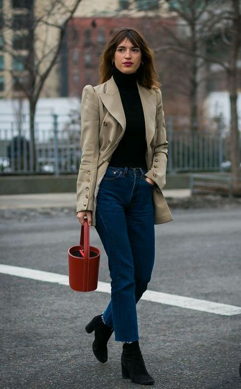 a black turtleneck, a tan vintage blazer with button sleeves, blue jeans, black sock boots and a red bucket bag