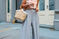 a blush silk spaghetti strap top, blue high wiasted wideleg pants, white shoes and a wicker bag