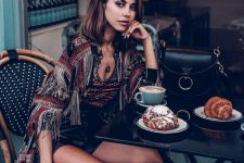 a boho printed top and a jacket with fringe, black leather shorts and burgundy leather boots