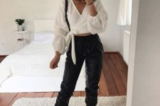 a bold outfit with a white crop blouse with puff sleeves, black joggers and white trainers